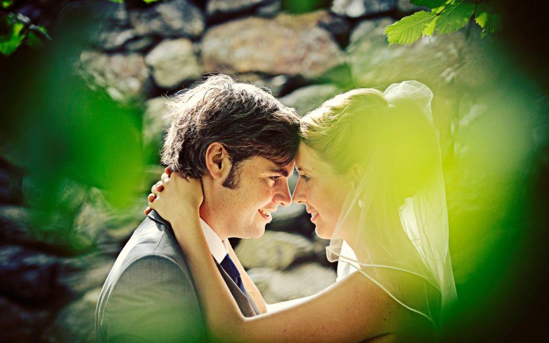 Bröllopsfoto från Marstrand. Par framför mur med löv i förgrunden.