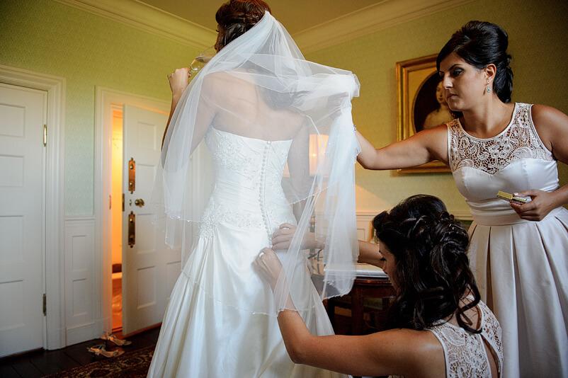 Brudens syster och svägerska hjälper till med slöjan inför ceremonin.